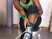 Busty black girl gives a footjob