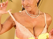 Busty mature blonde in yellow dress toys a hairy twat