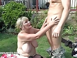 An older woman doing two guys outdoors